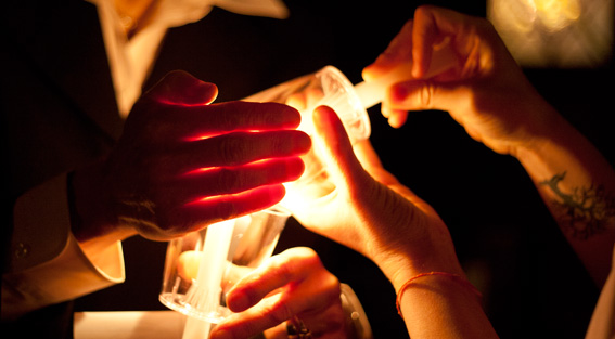 Hands lighting candles